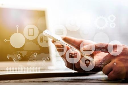Geschäftsmannhand, die an digitalem Tablet-Computer und intelligentem Telefon mit Geschäftsstrategie der digitalen Schicht und Social Media-Diagramm auf hölzernem Schreibtisch arbeitet