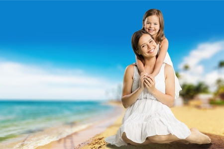 Healthy mother and baby girl pointing while sitting on beach in the evening Banco de Imagens