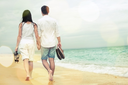 Young couple walking on sea coast in sunset