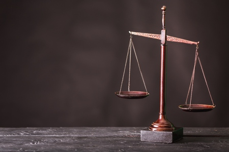Law scales on table on dark background