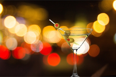 Martini in glass with olives on bokeh background
