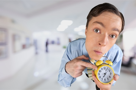 Frustrated young businessman holding an alarm clock Stock Photo