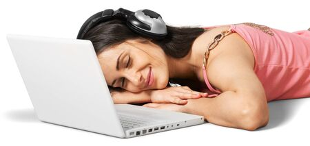 Young woman lying down in front of her laptop with headphones on Stock Photo