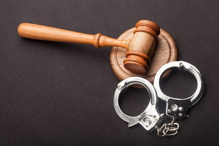 Gavel and handcuffs isolated on black