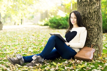Pretty relaxed young woman reading a book at the lawn with sun shining Stock Photo