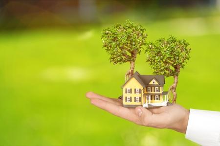 Sicheres Familienhausmodell und Garten auf Sohn Tochter Kinder Kind Vormund Mutter Vater Hände, verwischen natürlichen Grünbaum Pflanzumgebung Hintergrund: Home Loan Property Ownership Assurance-Konzept