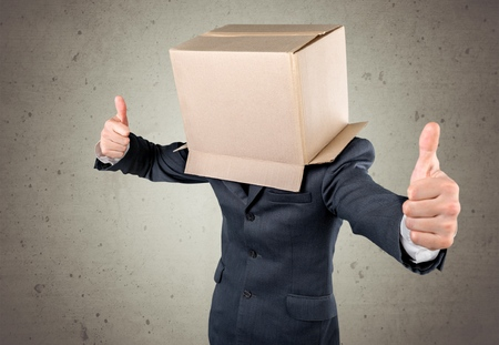 Businessman standing and gesturing with a cardboard box on his head with smiley face Stock Photo