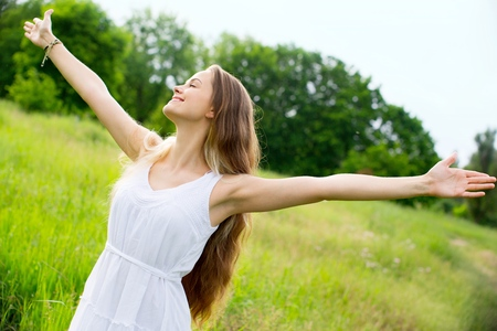 young woman with arms wide open in a field