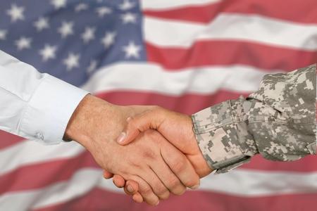 Amerikanischer Soldat im Uniform- und Zivilmannhandschlag