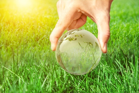 Earth in hand on green grass Stock Photo