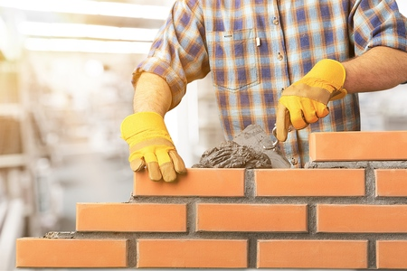 Industrial bricklayer installing bricks Standard-Bild
