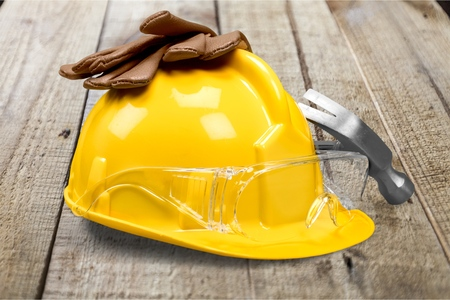 Working yellow hard hat, work gloves, safety glasses, ear plugs, hammer builder on a white background Stock Photo