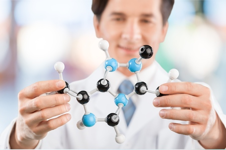 Closeup of schoolboy examining molecular structure in lab