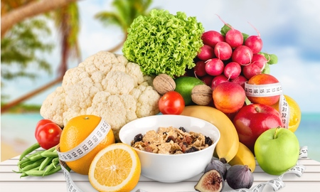 Diet weight loss breakfast concept with tape measure organic green apple, cereal bowl, orange juice, pineapple, muesli cereal bowl, pear, kiwi, lemon, rahat delight, strawberries on a white background