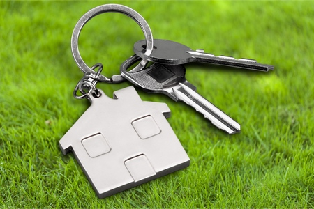 Two silver keys with metal house figure Stock Photo