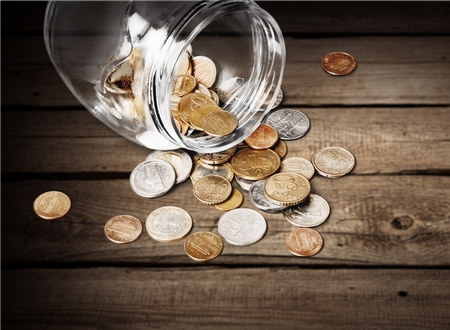 Jar of pennies spilling out on white Stock Photo