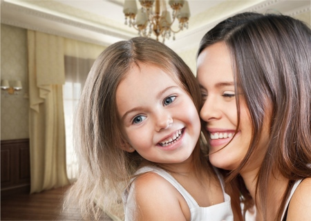 Mother and Baby kissing and hugging at Home. Happy Smiling Family Portrait. Mom and Her Child Having Fun together Stock Photo
