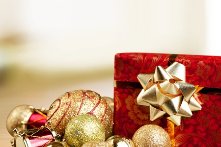 Christmas gift and baubles on defocused lights background Stock Photo