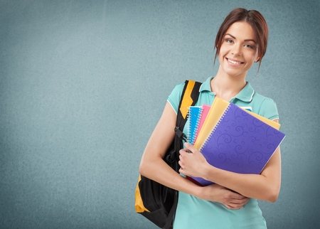 Beautiful student girl with backpack and books, isolated on white background Stock Photo