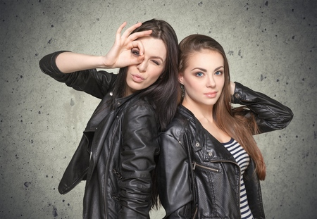 Two young girl friends standing together and having fun. Both showing signs with hands. Looking at camera. Inside