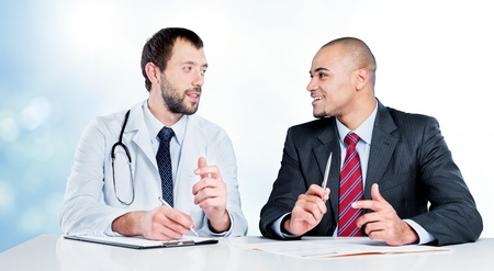 Mature Business group talking to a doctor in modern office Stock Photo