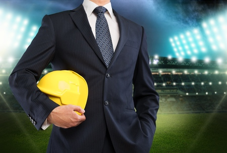 Elegant businessman holding a soccer ball, close up