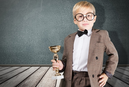 elementary school boy receiving a trophy in classroom with teachers and classmate Stock Photo
