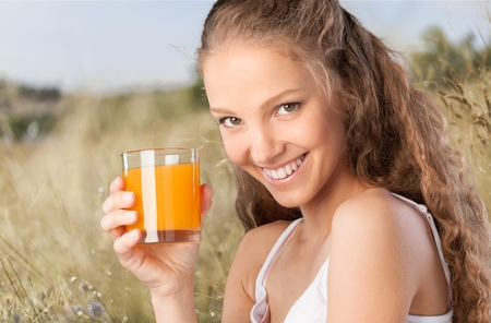 Young attractive happy woman with glass of juice