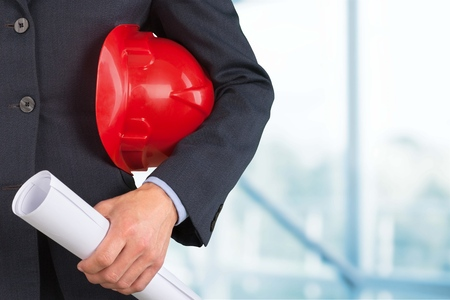 Close-up of businessman holding helmet and building project