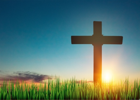 The cross on green grass with sunset Stock Photo