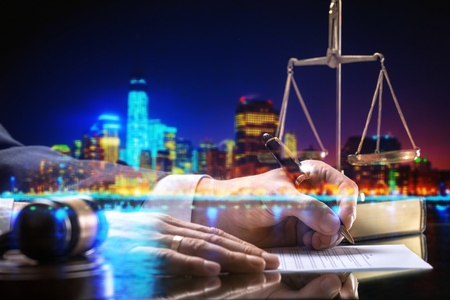 Businessman and wooden gavel on city background