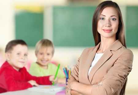 Young female teacher with schoolchild in classroom