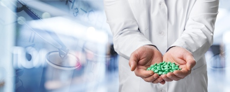Doctor holding pill in laboratory Stock Photo