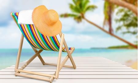 Towel and hat on a sun lounger with stripes, isolated on white background