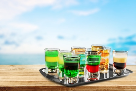 Several alcoholic shots of different drinks at a party in a nightclub on the counter Foto de archivo