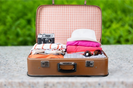 Retro tourist luggage with colorful clothes and copyspace on grungy background Stock Photo