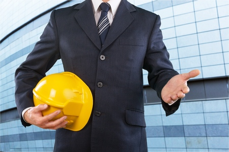 Male architect with yellow helmet showing greeting gesture. Partnership and engineering project concept.
