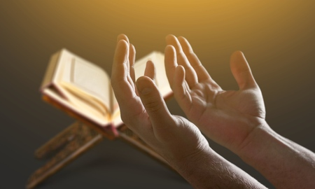 Muslim man hands holding rosary with quraan Stock Photo