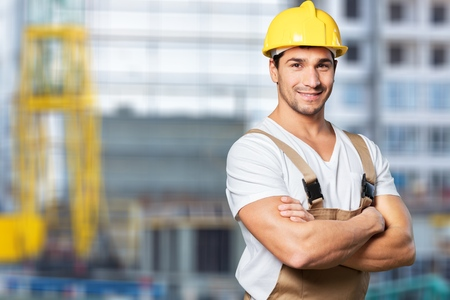 Smiling craftsman on building background