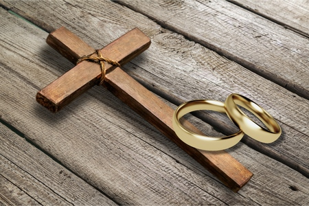 Wedding rings and cross on desk