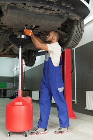 Mechanic Draining the Oil of a Car in an Oil Drain Tank