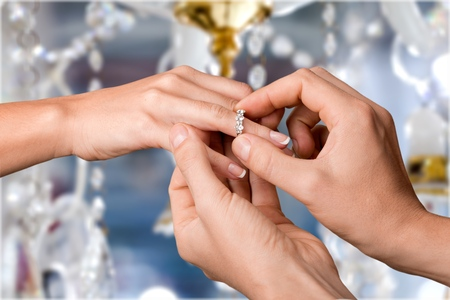 Close Up Of Male Hand Inserting An Engagement Ring Into A Finger Stock Photo