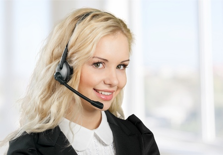 Smiling call center employee during a telephone conversation Archivio Fotografico