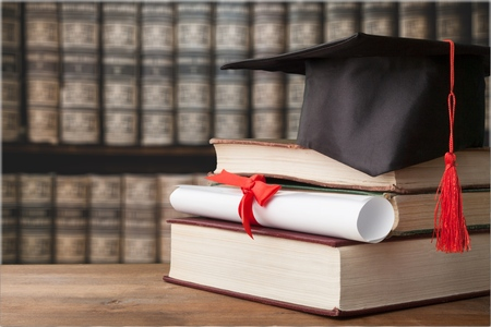 Graduate cap and book in library Stockfoto