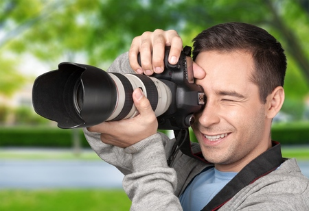 Happy young man clicking photo from camera