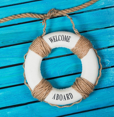Wir stellen ein ! - Willkommen an Bord - Rettungsring mit Netz und blauem Text auf Holzhintergrund