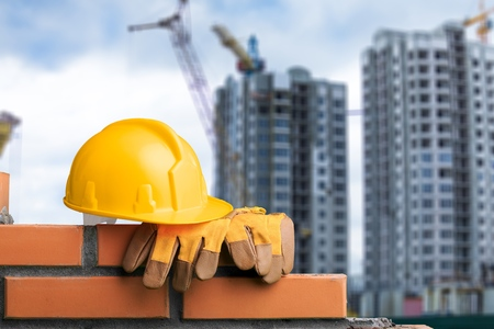 Yellow helmets on brickwork