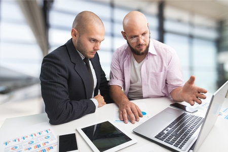 Two serious businessmen using laptop