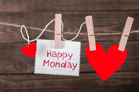 Happy Monday on instant paper and small red hearts hanging on the clothesline. On old wood background