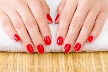 Manicure - nice manicured woman nails with red nail polish Standard-Bild